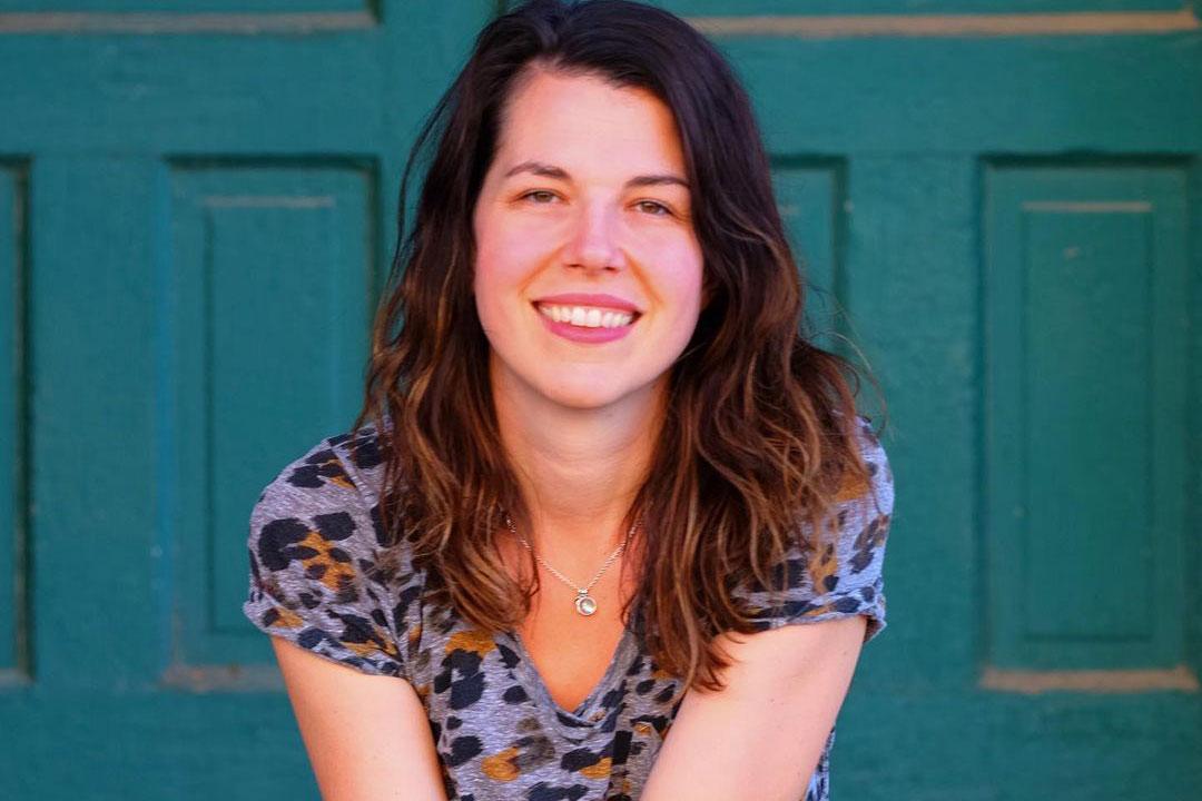 Dr. Laura Gouge sitting in front of blue door